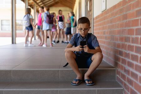 Front view of a Caucasian schoolboy wearing glasses, shorts, flip-flops and a rucksack sitting on a step by a wall in the schoolyard at elementary school using a smartphone, with other schoolchildren standing together in the background