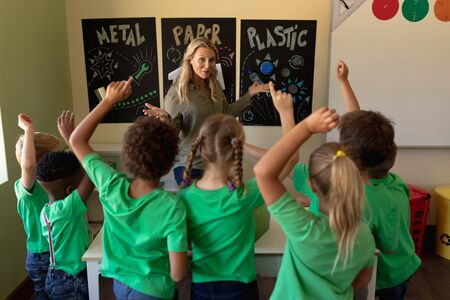 Vorderansicht einer kaukasischen Schullehrerin mit langen blonden Haaren, die auf ein Recycling-Plakat zeigt, und einer vielfältigen Gruppe von Schulkindern, die grüne T-Shirts von hinten tragen und die Hände heben, um während einer Unterrichtsstunde in einem Grundschulklassenzimmer eine Frage zu beantworten Standard-Bild