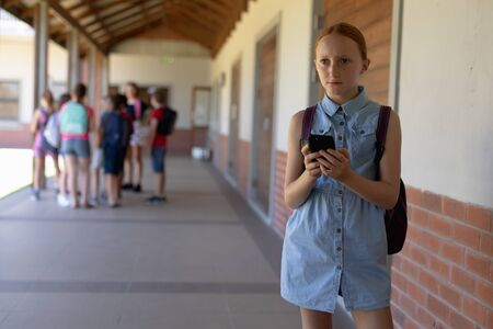 Front view of a Caucasian schoolgirl wearing a blue dress and a rucksack standing in the schoolyard at elementary school using a smartphone, with other schoolchildren standing together in the background Standard-Bild