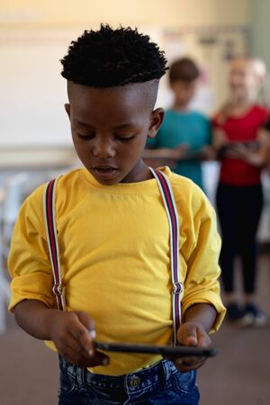 Front view close up of an African American schoolboy wearing a yellow shirt and braces standing and using a tablet computer in an elementary school classroom, with classmates standing in the backgroun