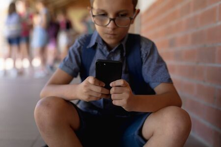 Front view close up of a Caucasian schoolboy wearing glasses, shorts and a rucksack sitting by a wall in the schoolyard at elementary school using a smartphone, with other schoolchildren standing together in the background