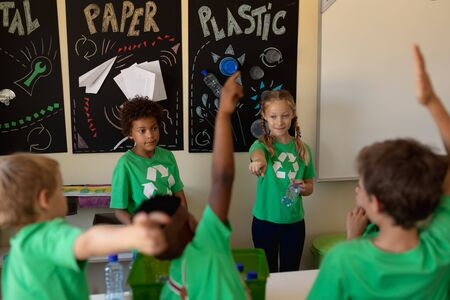 Rear view of a diverse group of schoolchildren wearing green t shirts raising hands to question a Caucasian and an African American schoolgirl standing in front of posters about recyclable materials in an elementary school classroom
