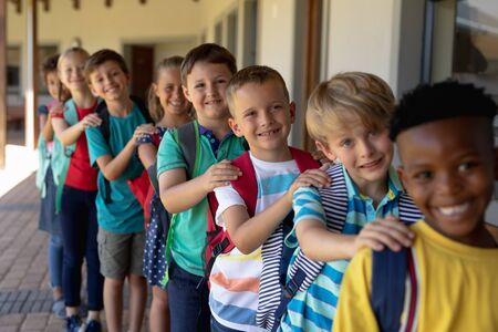 Front view of a diverse group of schoolchildren walking single file with hands on each others shoulders along an outdside corridor between classrooms at an elementary school, looking to camera and smiling Reklamní fotografie