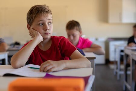 Front view close up of a Caucasian schoolboy with short hair wearing a red t shirt sitting at a desk in an elementary school classroom leaning on his hand and looking away, an open book on the desk in