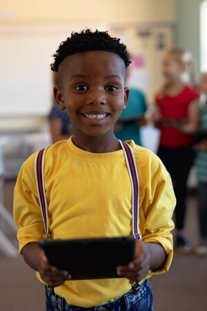 Front view close up of an African American schoolboy wearing a yellow shirt and braces standing using a tablet computer, looking to camera and smiling in an elementary school classroom, with classmate