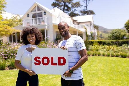 Front view of a mixed race couple standing in the garden, smiling to camera and holding sign with the word sold written on it