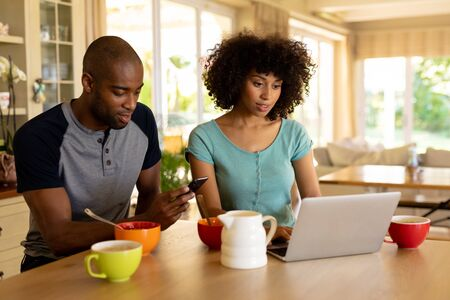 Front view of a mixed race couple sitting in the kitchen, using laptop and a mobile phone whiel they have breakfast