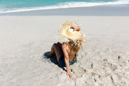 Front view of a Caucasian woman wearing a straw hat, reclining on the beach with blue sky and sea in the background, sunbathing