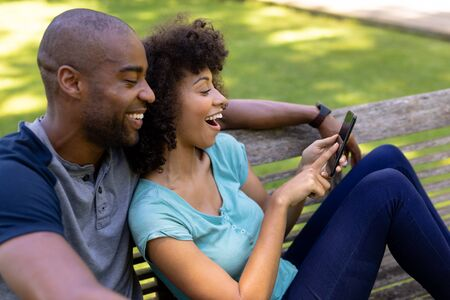 Side view cloxe up of a mixed race couple sitting on a bench in the garden, laughing and looking at a mobile phone together