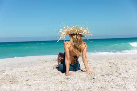 Rear view of a Caucasian woman wearing a straw hat, reclining on the beach with blue sky and sea in the background, sunbathing