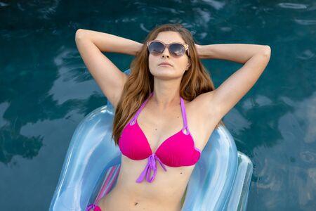 Vooraanzicht close-up van een blanke vrouw die strandkleding en zonnebril draagt, liggend op een opblaasbare ligstoel die op een zonnige dag in een zwembad zonnebaadt, met haar handen achter haar hoofd Stockfoto