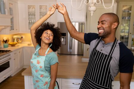 Front view of a mixed race couple at home dancing in the kitchen wearing aprons and smiling at each other Imagens