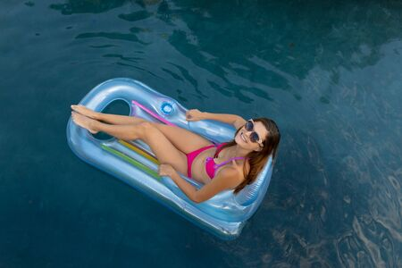 High angle view of a Caucasian woman wearing beachwear and sunglasses sitting on an inflatable pool lounger sunbathing in a swimming pool on a sunny day 免版税图像