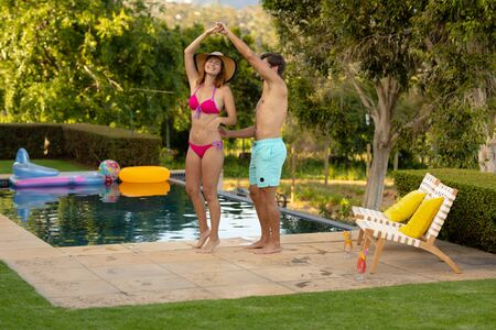Front view of a Caucasian couple wearing beachwear holding hands and dancing in a garden beside a swimming pool and smiling