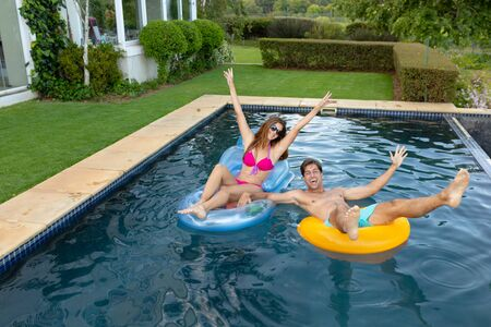 Front view of a Caucasian couple wearing beachwear having fun on inflatables in a swimming pool on a sunny day