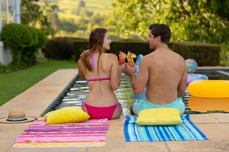 Rear view of a Caucasian couple wearing beachwear sitting in a garden beside a swimming pool, holding cocktails, making a toast and looking at each other smiling