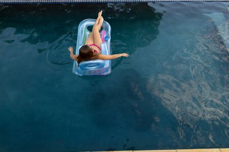 Rear view of a Caucasian woman wearing beachwear and sunglasses lying on an inflatable pool lounger sunbathing in a swimming pool on a sunny day, dipping her hands in the water