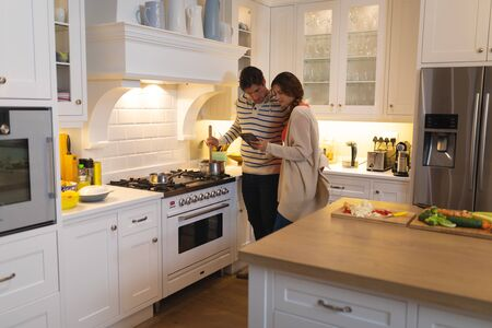 Side view of a Caucasian couple at home, standing in the kitchen cooking, the man stirring a pan on the hob and the woman showing him a tablet computer