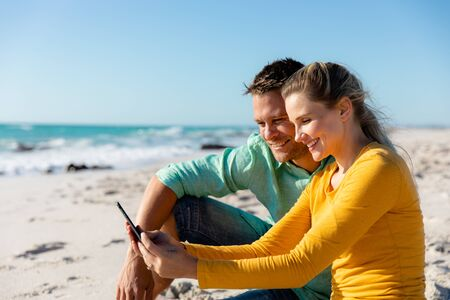Side view of a Caucasian couple reclining on the beach with blue sky and sea in the background, embracing and looking at their smartphone