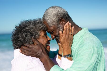 Side view close up, of a senior African American couple standing on the beach with blue sky and sea in the background, smiling at each other, touching heads and holding each others faces