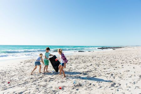 Front view distant of Caucasian siblings on the beach with blue sky and sea in the background, picking up the rubbish and putting it into a trash bag