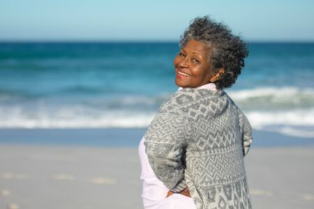 Portrait of a senior African American woman standing on the beach with blue sky and sea in the background, turning around with hands on hips and smiling to camera