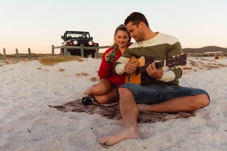 Front view of a Caucasian couple reclining on the beach, with an open top car in the background, the man holding the guitar, the woman holding a bottle of beer 版權商用圖片