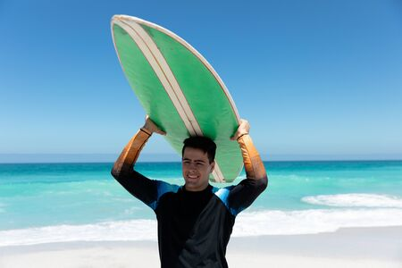 Front view of a Caucasian man walking on the beach with blue sky and sea in the background, carrying a surfboard over his head