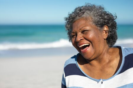 Front view close up of a senior African American woman standing on the beach laughing, with blue sky in the background