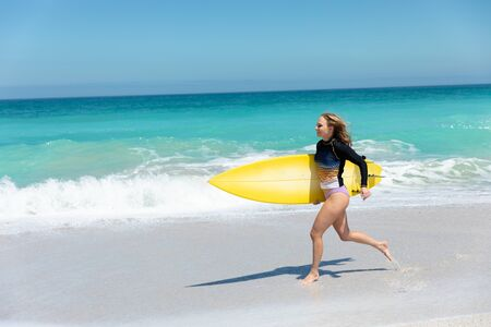 Side view of a Caucasian woman running on the beach with blue sky and sea in the background, holding a surfboard Standard-Bild