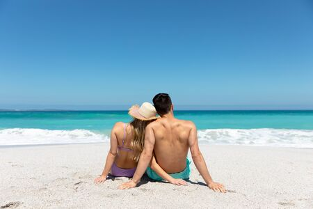 Rear view of a Caucasian couple reclining on the beach with blue sky and sea in the background, embracing and looking away