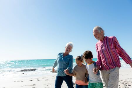 Side view of a multi-generation Caucasian family on the beach with blue sky and sea in the background, smiling, walking and holding hands 版權商用圖片