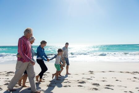 Side view of a multi-generation Caucasian family on the beach with blue sky and sea in the background, walking, embracing and holding hands