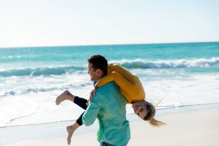 Side view of a Caucasian man carrying his Caucasian girlfriend over his shoulder, walking on the beach with blue sky and sea in the background, smiling