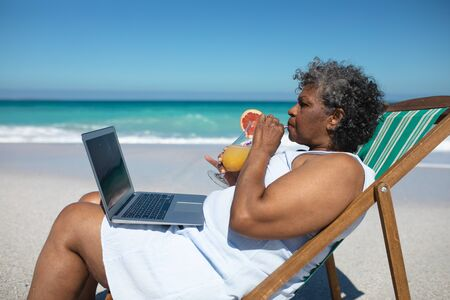 Side view of a senior African American woman on a beach in the sun, sitting in a deckchair, using a laptop computer and drinking a cocktail, with blue sky and calm sea in the background
