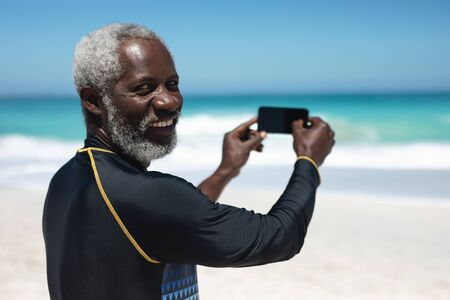 Rear view close up of a senior African American man on a beach in the sun, using a smartphone to take a photo, turning and smiling to camera, with blue sky and sea in the background Archivio Fotografico