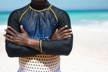 Front view mid section of a senior African American man standing on a beach in the sun, wearing a wetsuit with ams crossed, blue sky and sea in the background