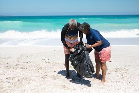 Vue latérale d'un couple afro-américain âgé sur une plage au soleil, tenant un sac poubelle noir et ramassant les déchets du sable, avec un ciel bleu et une mer calme en arrière-plan