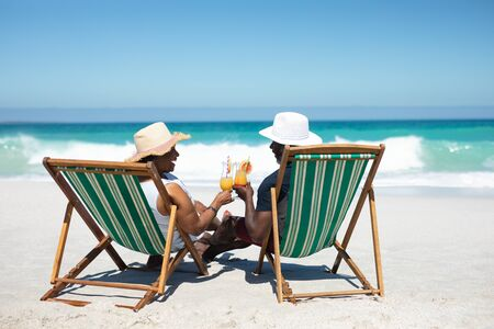 Rear view of a senior African American couple on a beach in the sun, sitting in deckchairs, wearing sun hats, holding cocktails and making a toast, with blue sky and calm sea in the background