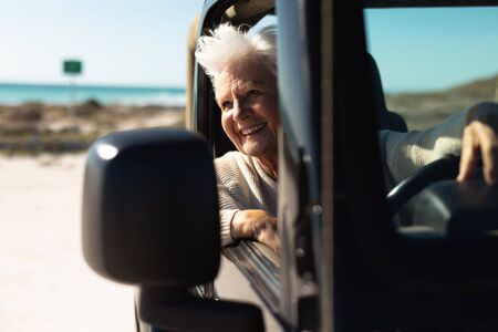 Front view of a senior Caucasian woman at the beach in the sun, sitting behind the wheel in the driving seat of a car, looking out of the side window and smiling