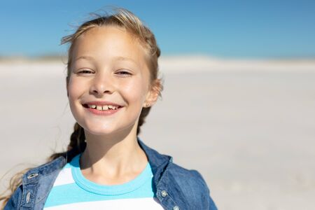 Portrait close up of a Caucasian girl on a sunny beach, smiling to camera, with blue sky and sand in the background Stockfoto