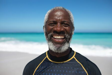 Portrait of a senior African American man on a beach in the sun, looking to camera and smiling, with blue sky and sea in the background Standard-Bild