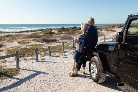 Side view of a senior Caucasian couple at the beach in the sun, standing and embracing, leaning against their car and admiring the view