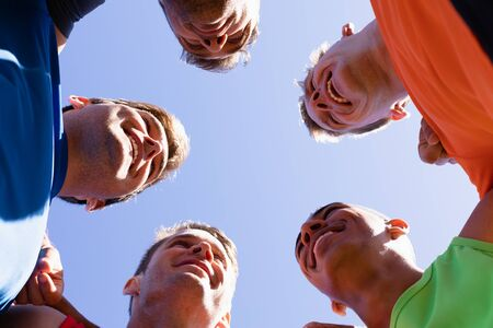 Low angle view of a multi-ethnic group of male runners training at a sports field, in a motivational huddle, with arms around shoulders, smiling in the sun against blue sky