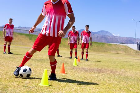 Front view close up of a group of Cacuasian male football players wearing a team strip, training at a sports field in the sun, waiting their turn to dribble a football between cones, with blue sky in the background