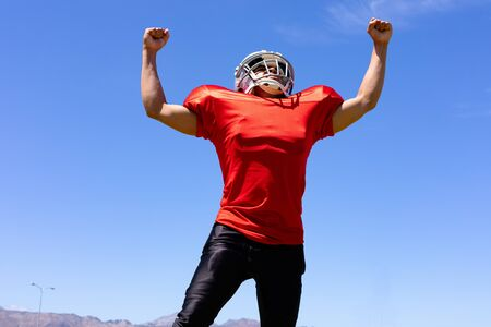 Low angle front view of a mixed race male American football player wearing a team uniform, training at a sports field, raising arms with fists clenched, celebrating a victory, with blue sky in the background