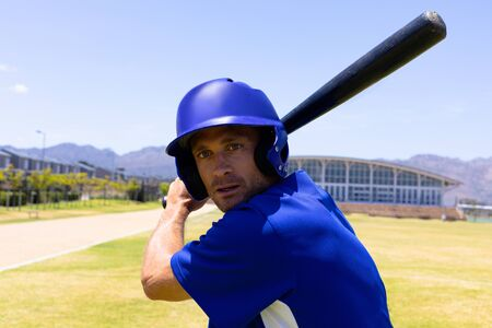 Portrait close up of a Caucasian male baseball player, a hitter, wearing a team uniform and helmet, training at a sports field, holding a baseball bat ready to swing at a pitch, looking straight to camera, with blue sky in the background