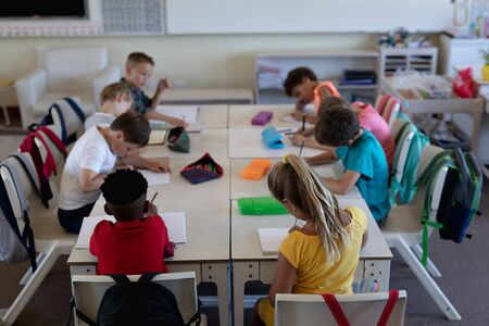 Diverse elementary school. High angle view of a diverse group of schoolchildren sitting at desks working in an elementary school classroom Standard-Bild