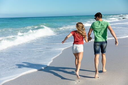Rear view of a Caucasian couple on the beach with blue sky and sea in the background, running. Weekend beach vacation, lifestyle and leisure.