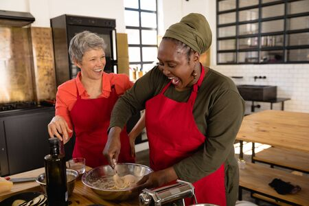 Front view of a Caucasian and an Senior African American woman preparing food at a cookery class, laughing and talking, while the African American woman mixes dough in a bowl Stock Photo